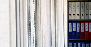 Aktenordner im Regal und Lamellen Vorhang Büro