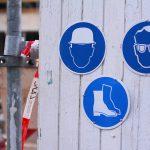 Baustellenzaun mit Arbeitsschutz Schildern Helm Brille Schuhe