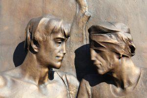 Bild zweier Bronze Statuen die rechte hat einen Verband um die Augen